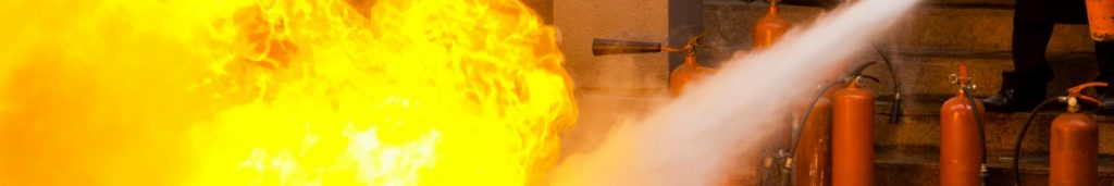 Instructor demonstrates proper fire extinguisher techniques while battling a planned fire during a spanish safety course.