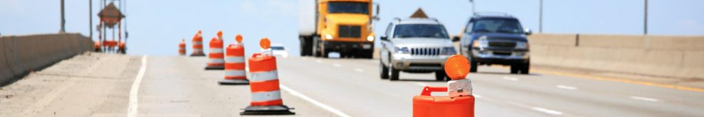Work zone on a highway with actual vehicles and traffic control measures in effect as taught in this Spanish safety course.