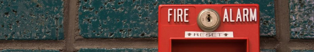 Red fire alarm on a blue brick building, illustrating the importance of fire prevention techniques.